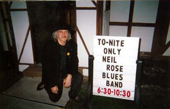 Neil Rose outside with Sign